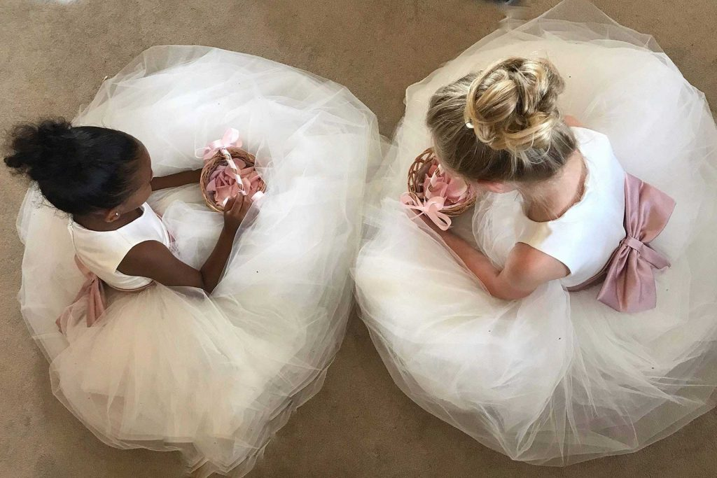 Two young bridemaids take a minute to sit down on the floor