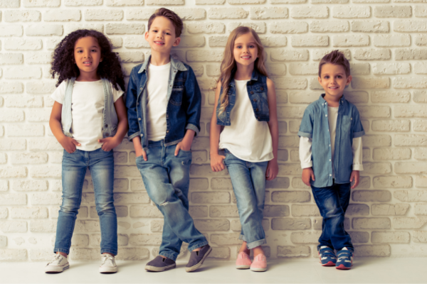 Children dressed in denim leaning against a wall