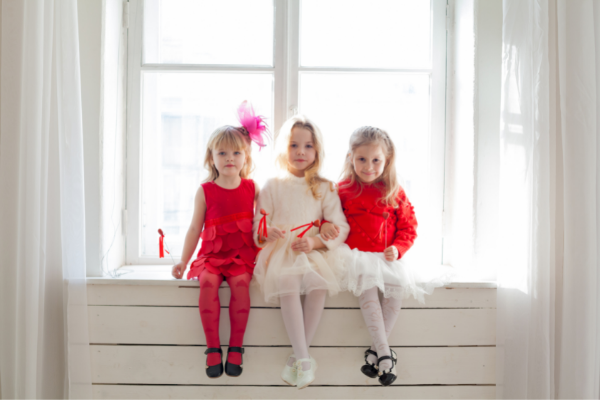Three little girls dressed and ready for a party